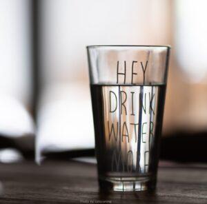 szklanka z napisem: hey, drink water more